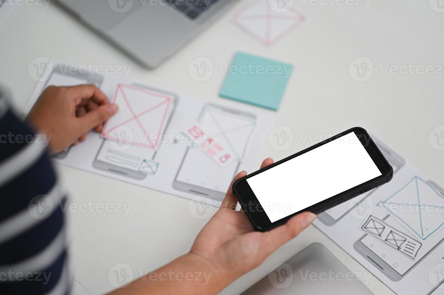applikationsdesigners designar på smartphone -appar. foto