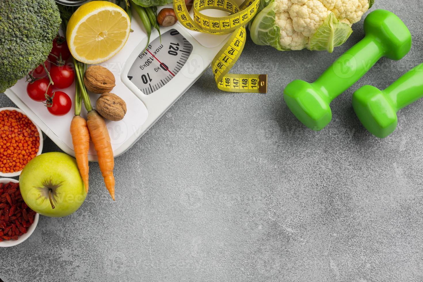 skala, vikter, frukt och grönsaker med kopieringsutrymme foto