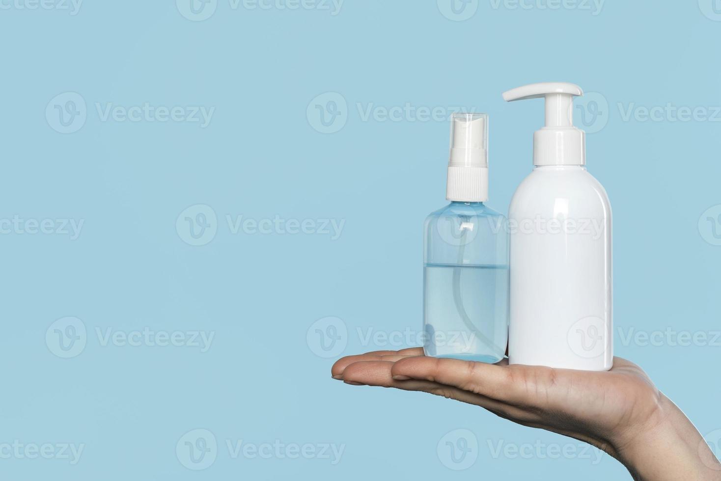 kvinna som håller desinfektionsflaskor foto