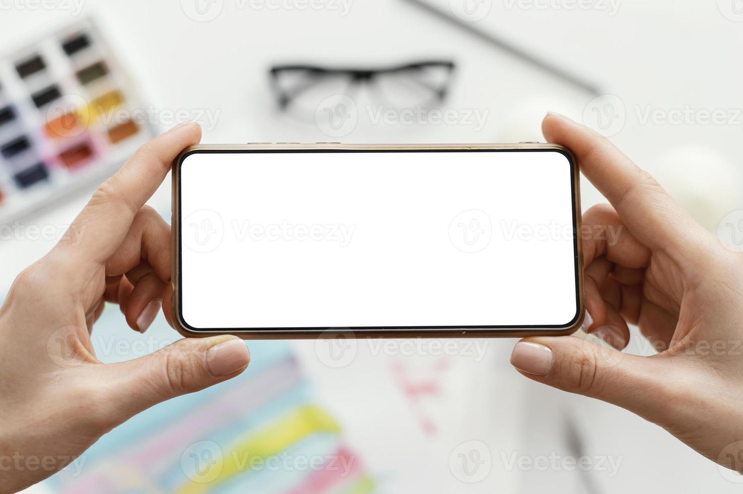 kvinna som tar ett foto av hennes konst med sin telefon