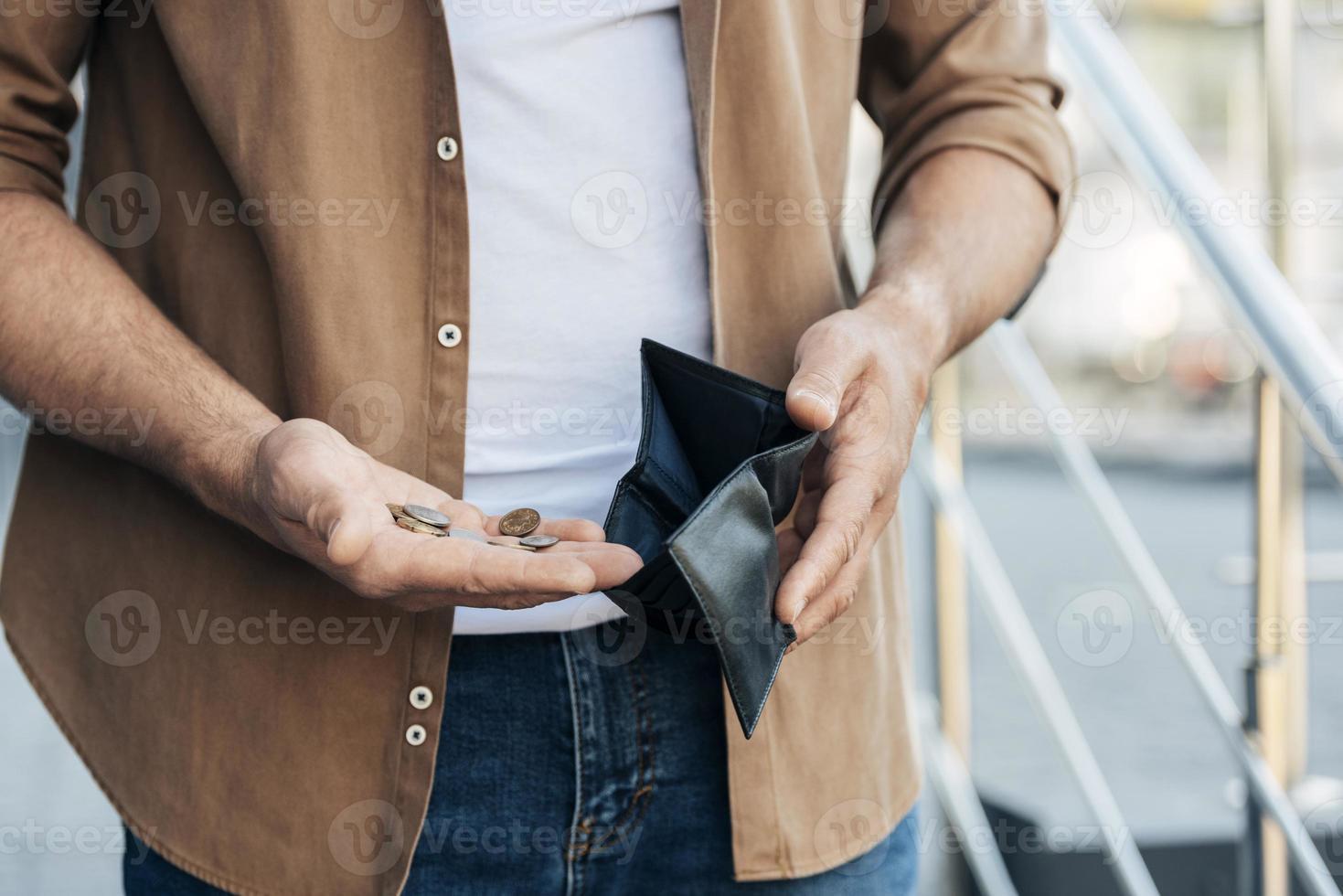 närbild av händer som håller plånbok och mynt foto