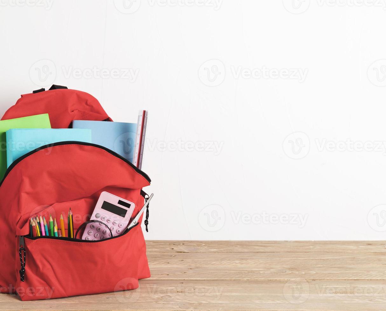röd skolväska med viktiga tillbehör foto