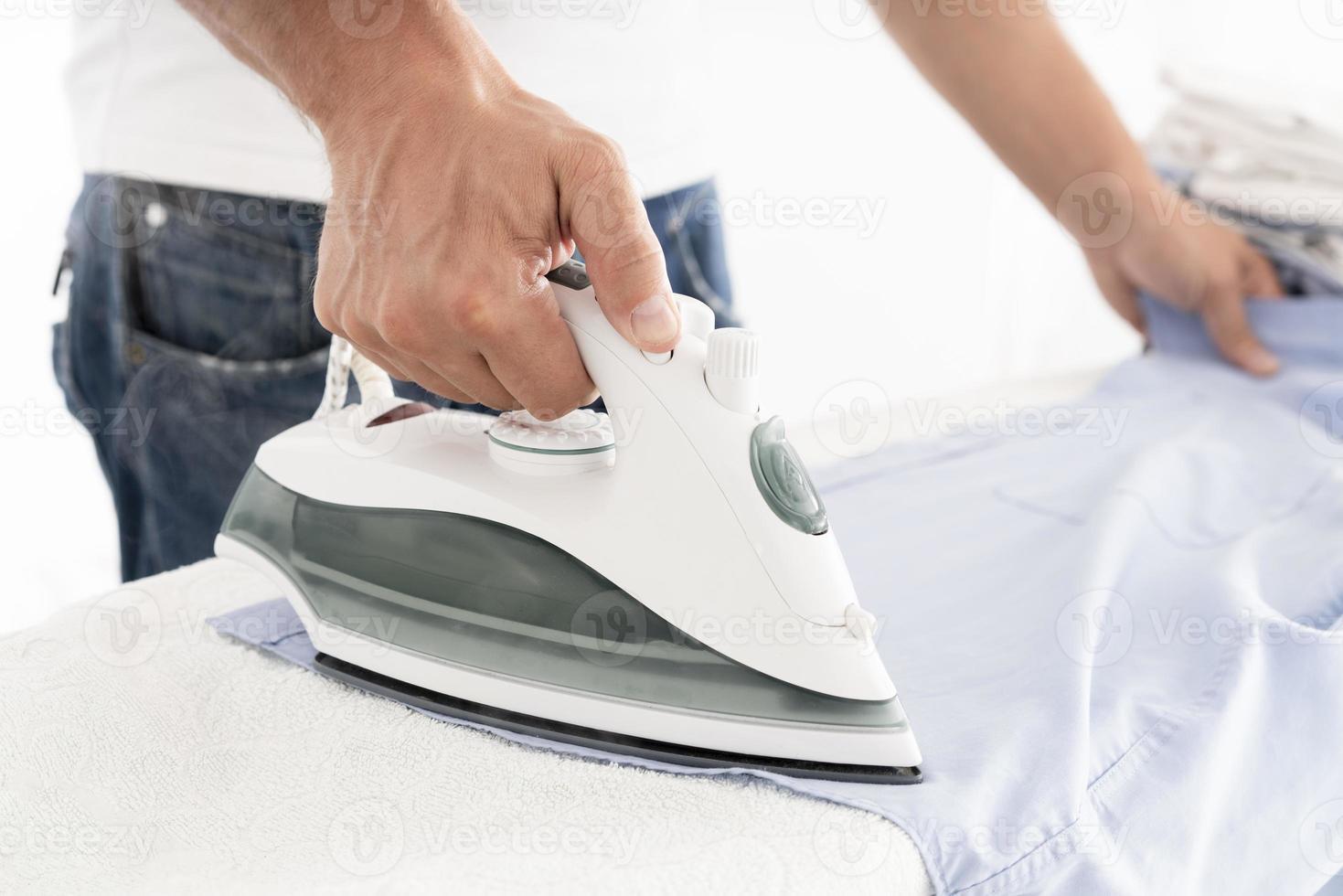 oigenkännlig man som stryker kläder foto
