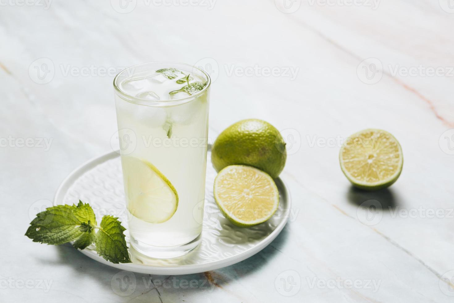 limonadglas och limefrukter foto