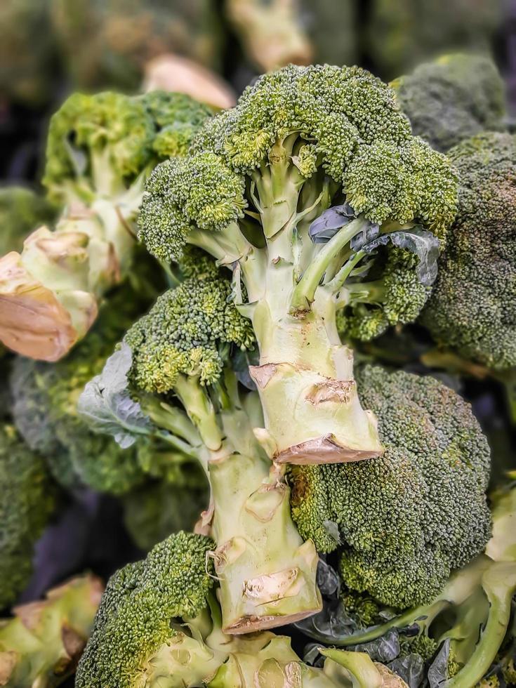 färsk broccoli i en hög på stormarknaden, hälsosam färsk grön rå broccoli. bakgrund, textur. foto