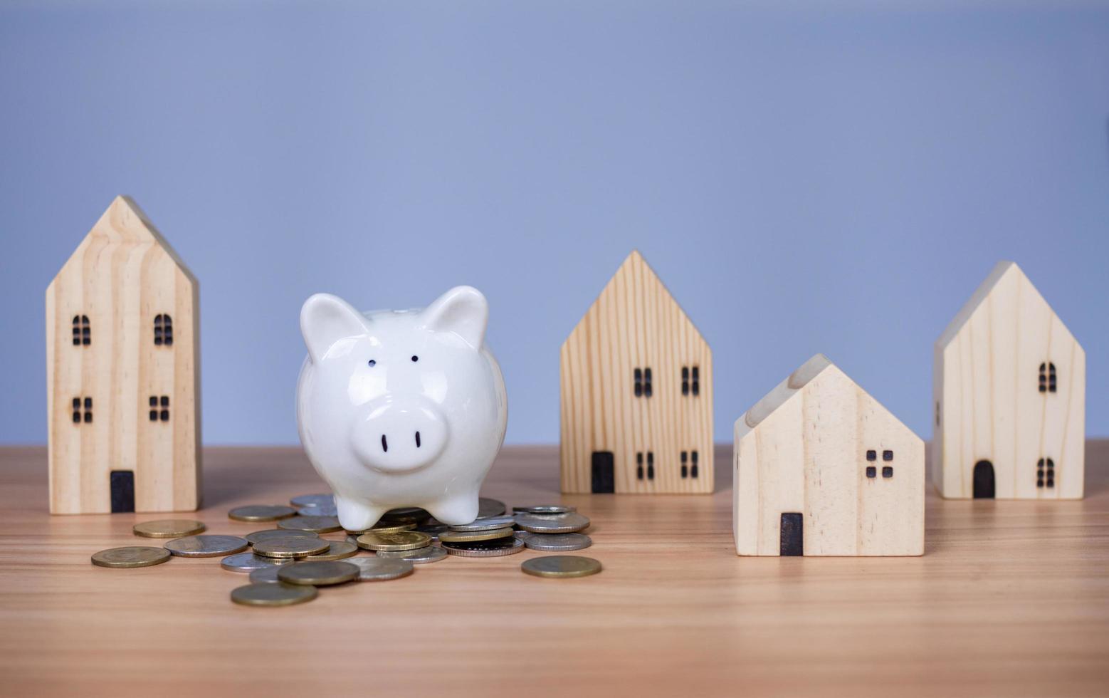 en vit spargris läggs på en hög med mynt. och bredvid är det ett modellhus i trä på en vit bakgrund. som alla ligger på ett träbord foto