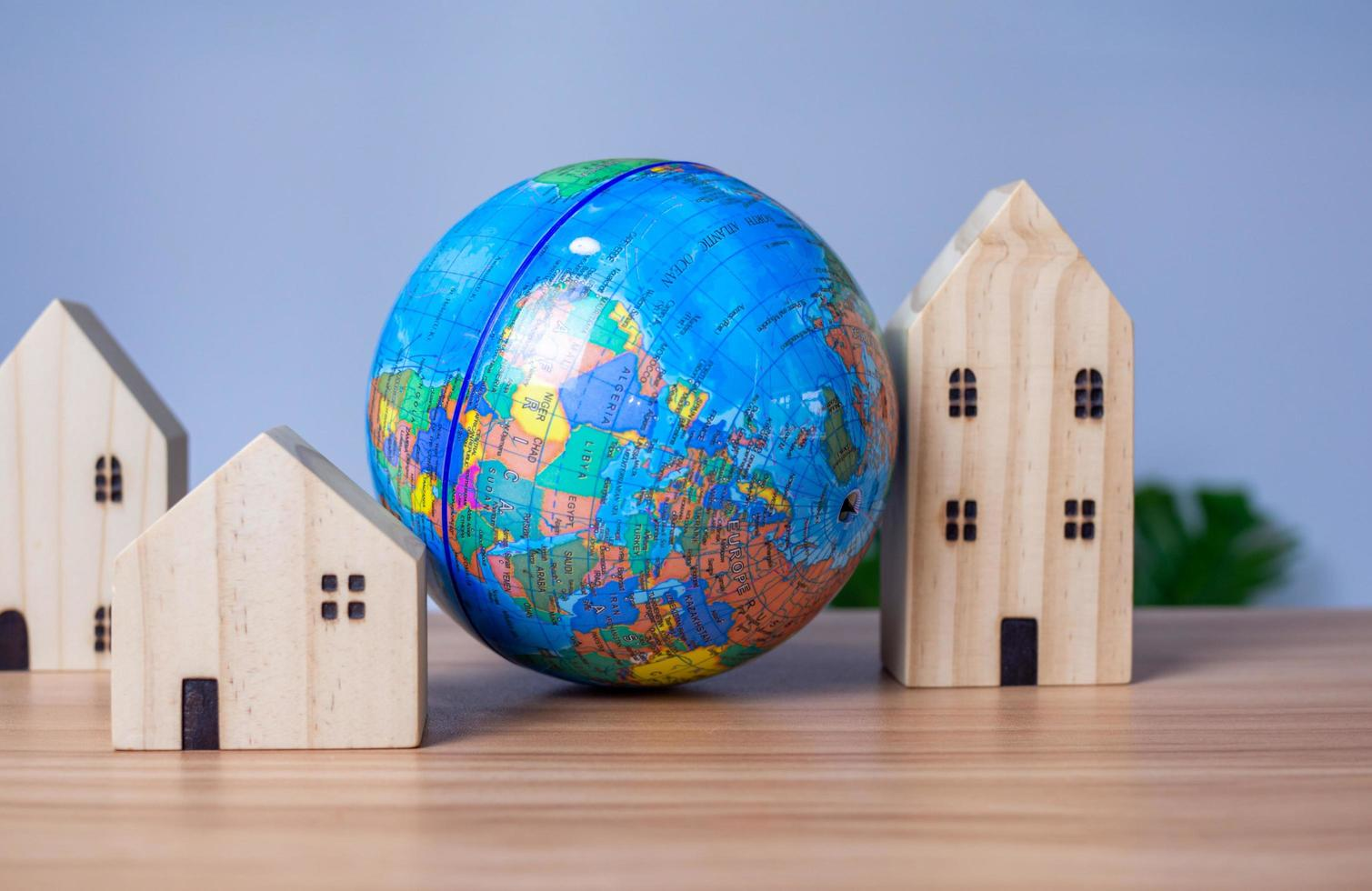 ett trä modellhus placeras bredvid en kopia jordglob. placerad på ett träbord med en ljusgrå bakgrund. rädda världskonceptet foto
