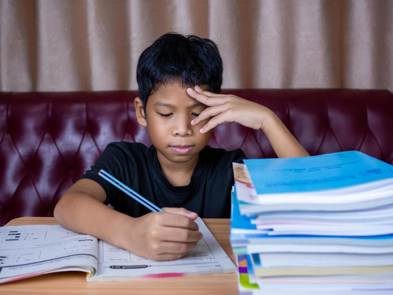pojke gör läxor och läser på ett träbord med en hög med böcker bredvid bakgrunden är en röd soffa och gräddgardiner. foto