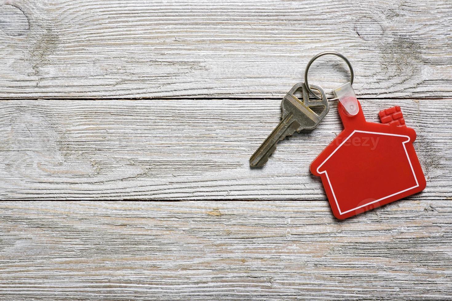 husnyckel med rött husform nyckelring för fastighetskoncept foto