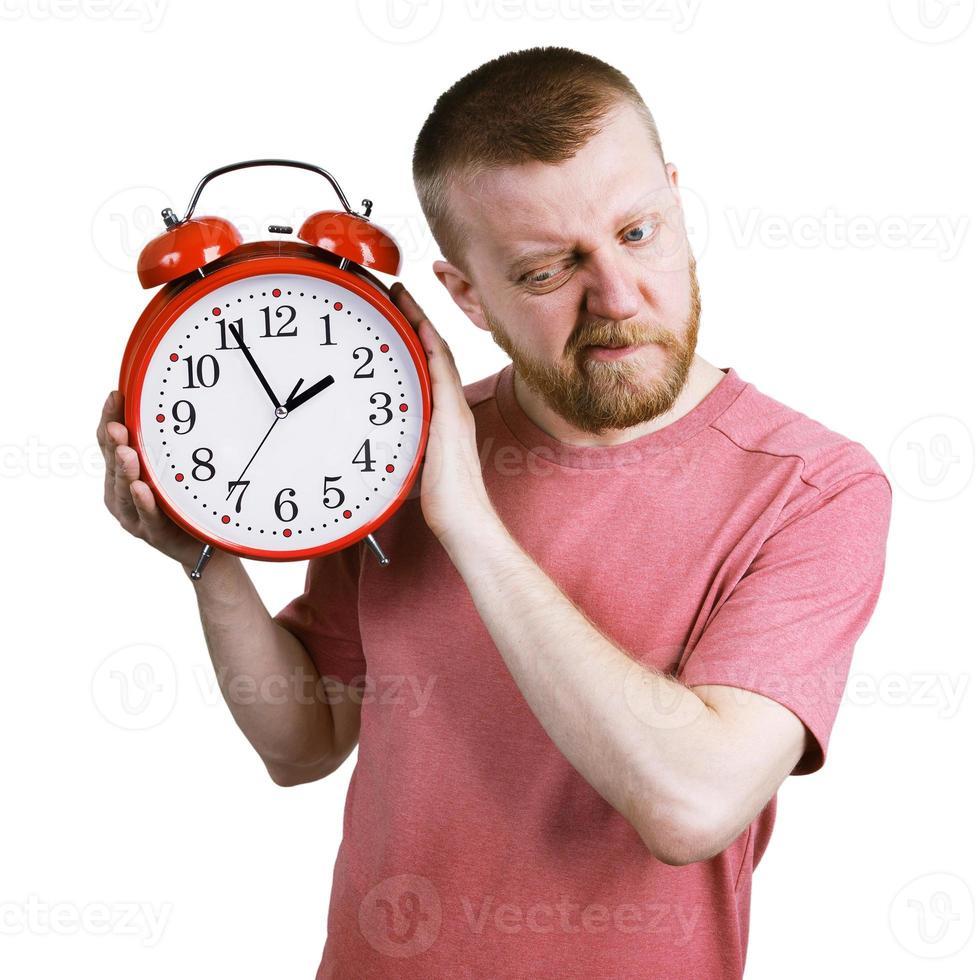 man lyssnar på väckarklockans tickande foto