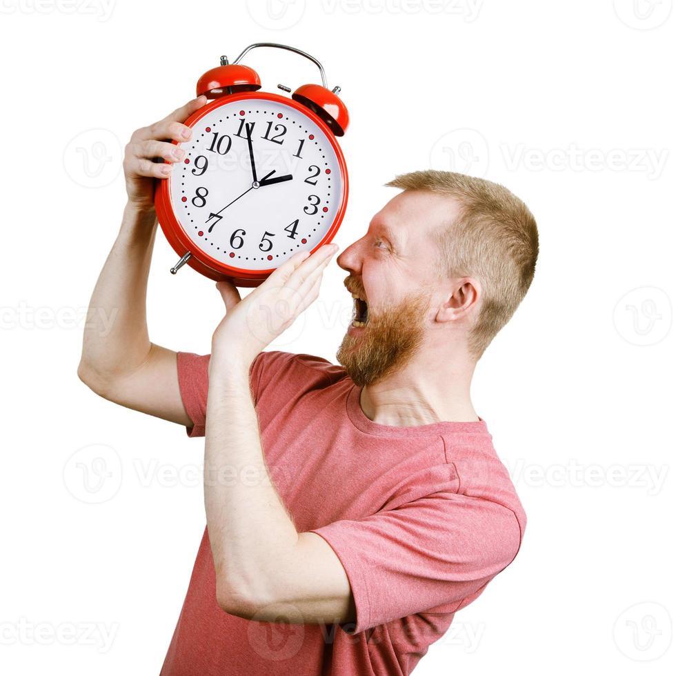 argar en skäggig man vill äta en väckarklocka foto