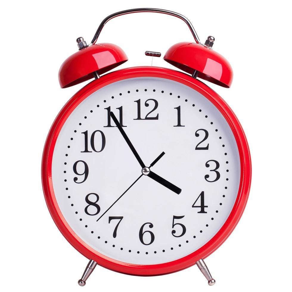 röd väckarklocka visar fem minuter till fyra foto