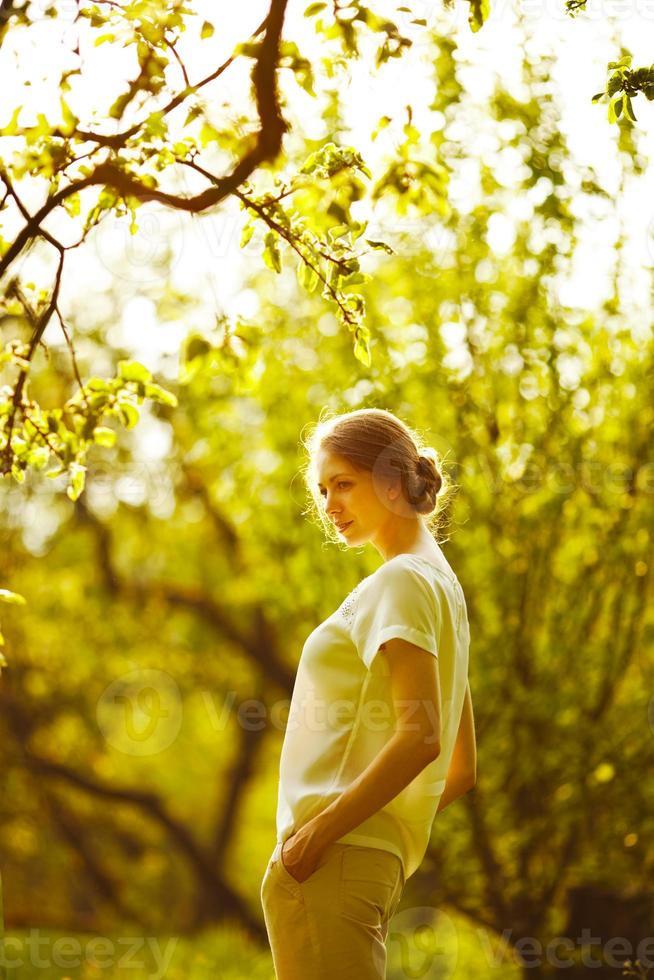 glad tjej står i sommarträdgården foto