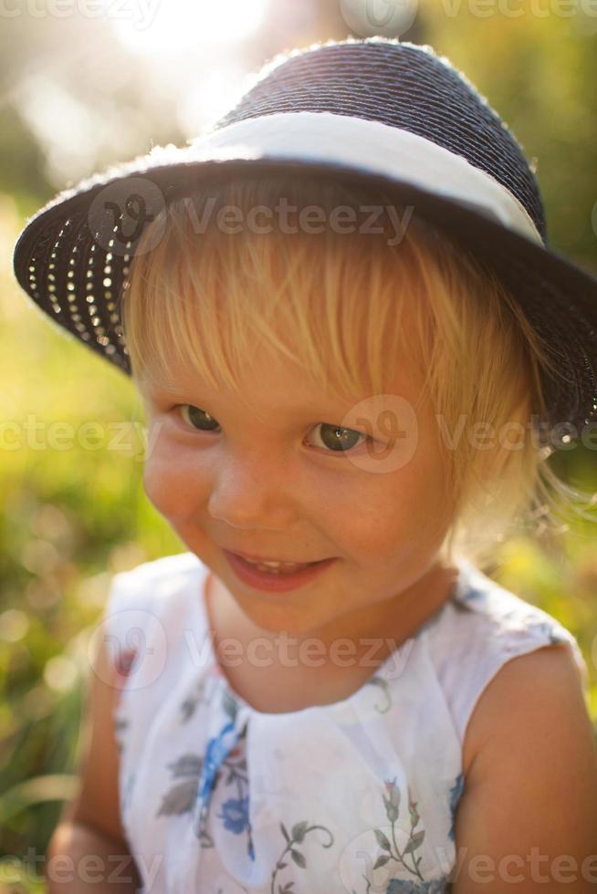 söt liten blond leende flicka i en blå hatt foto