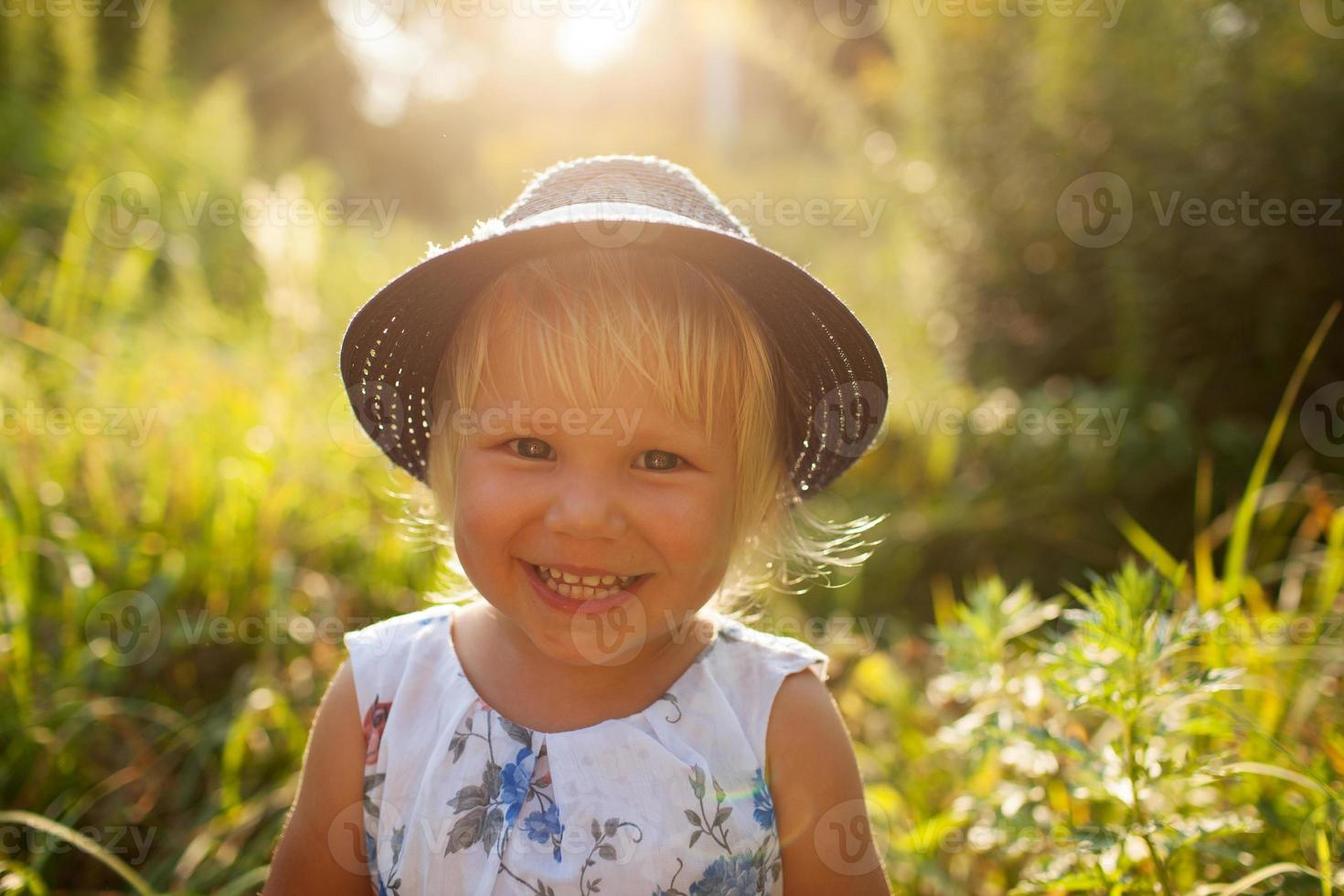liten blond tjej i en blå hatt foto