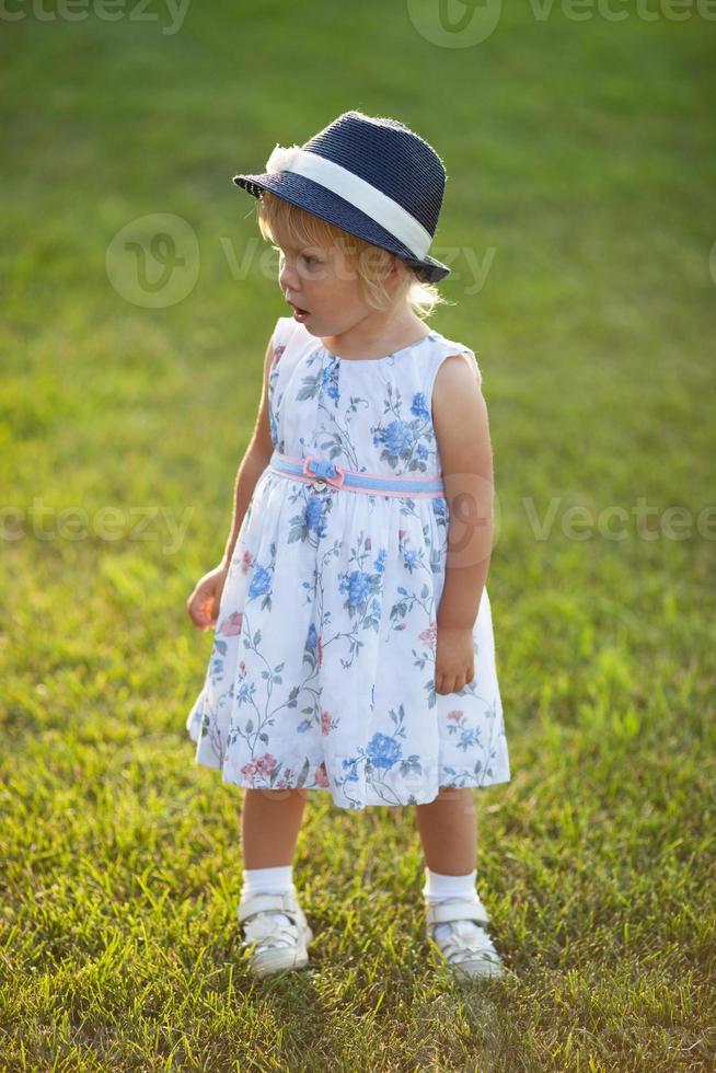 liten flicka i en klänning och hatt foto