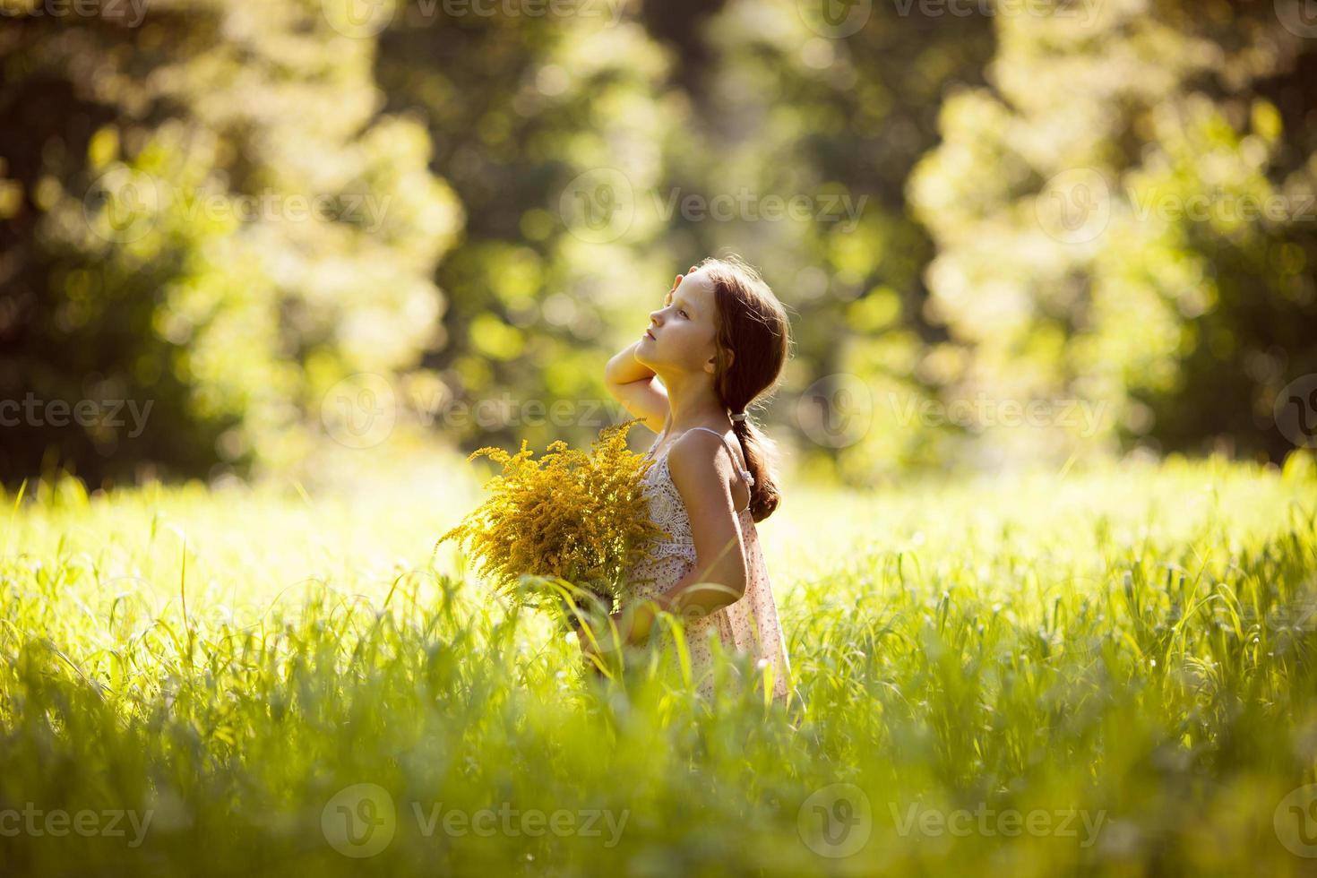 liten flicka som står med en bukett gula blommor foto
