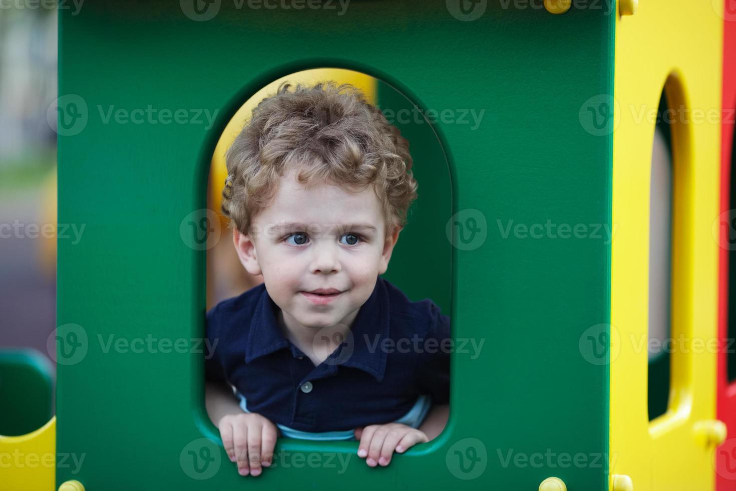 liten pojke gömmer sig i en lekstuga foto
