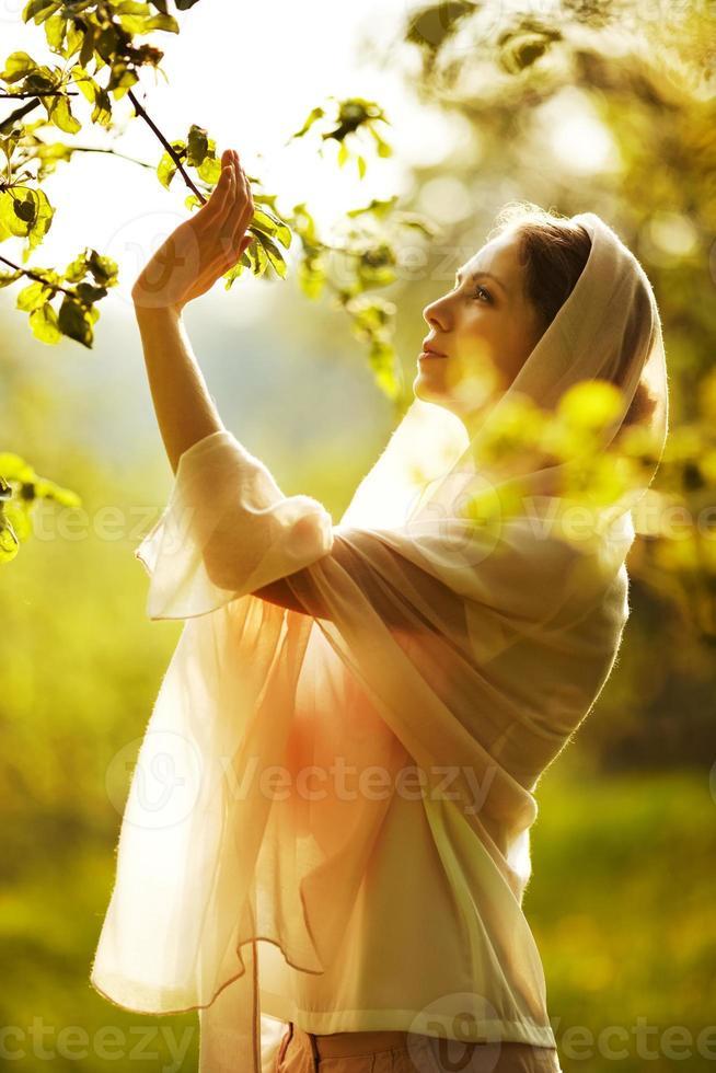 glad kvinna i en sommar trädgård foto