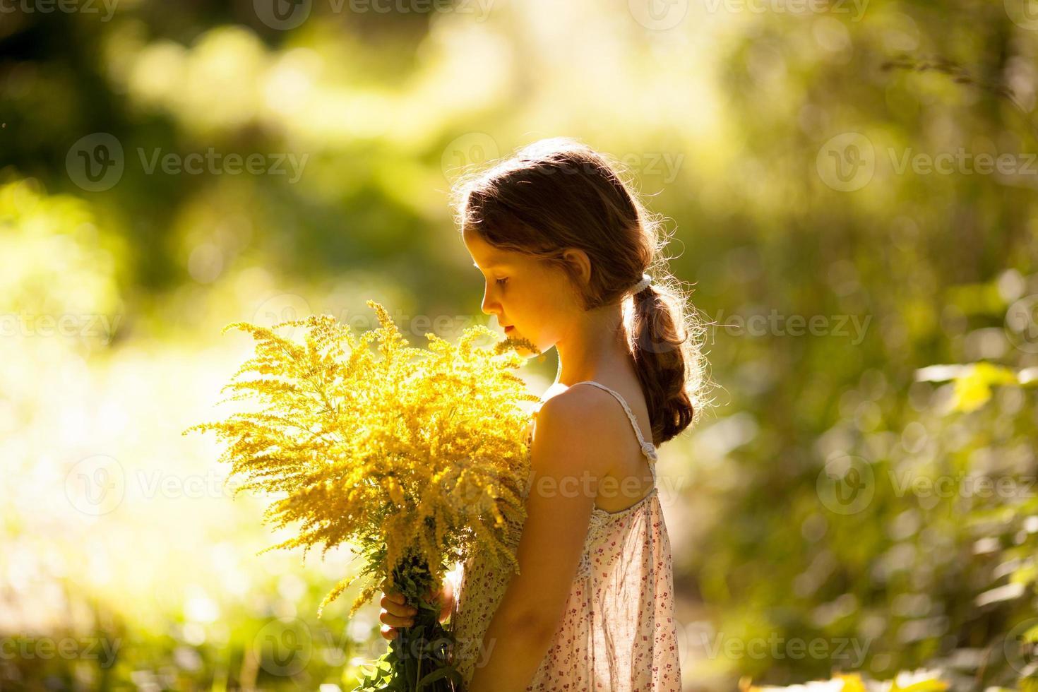 liten flicka som står med en bukett vildblommor foto