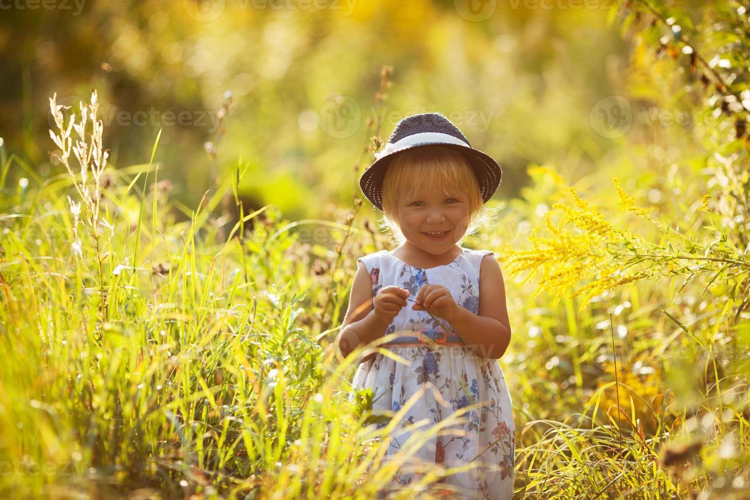 liten blond tjej i en klänning och hatt foto
