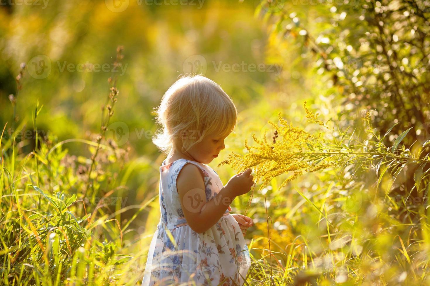 liten blond tjej i en klänning foto