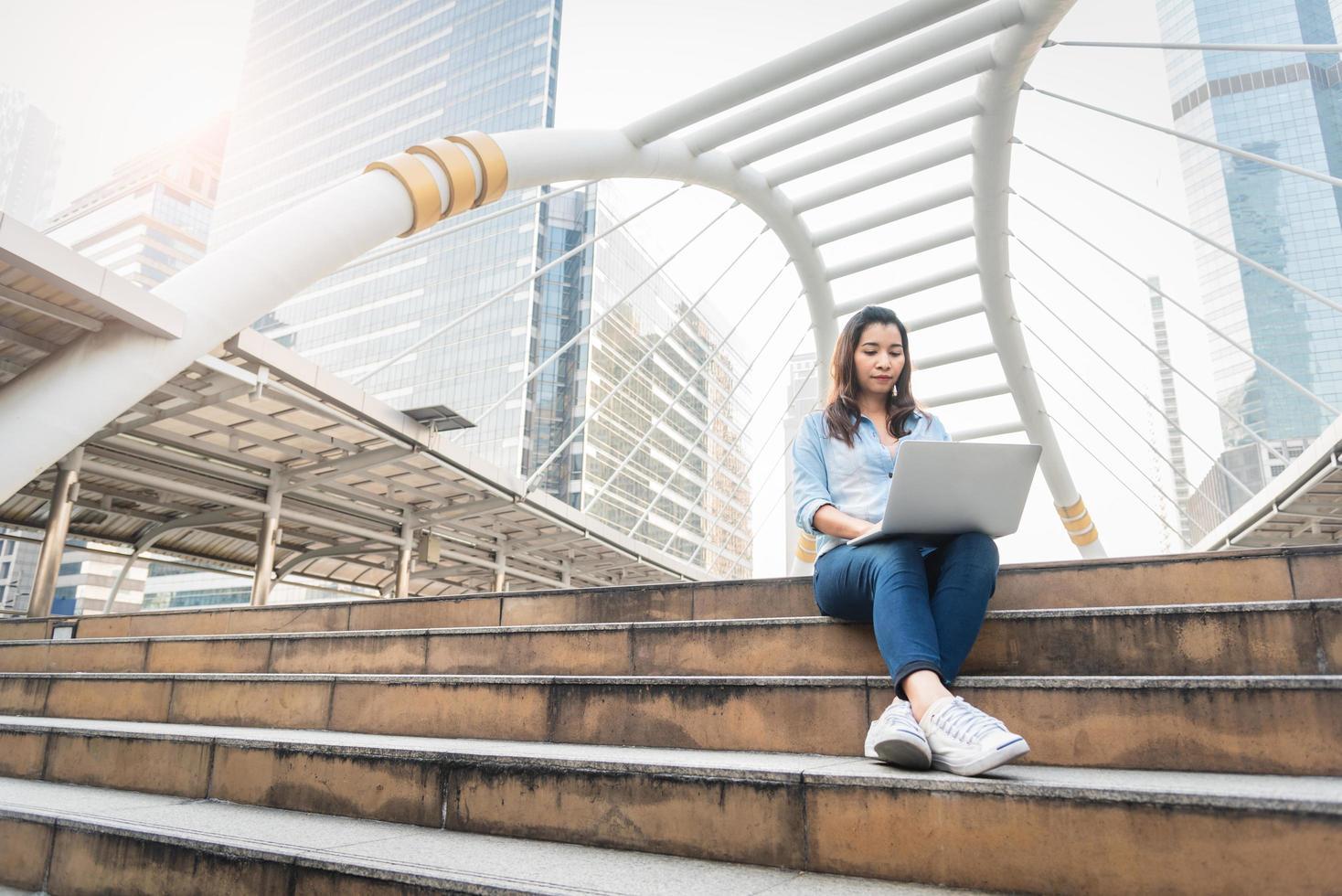 glad kvinna som arbetar med bärbar dator. framgångsrikt och lyckokoncept. teknik och livsstilskoncept stad och urbana tema. lyckligt liv på utomhus tema foto