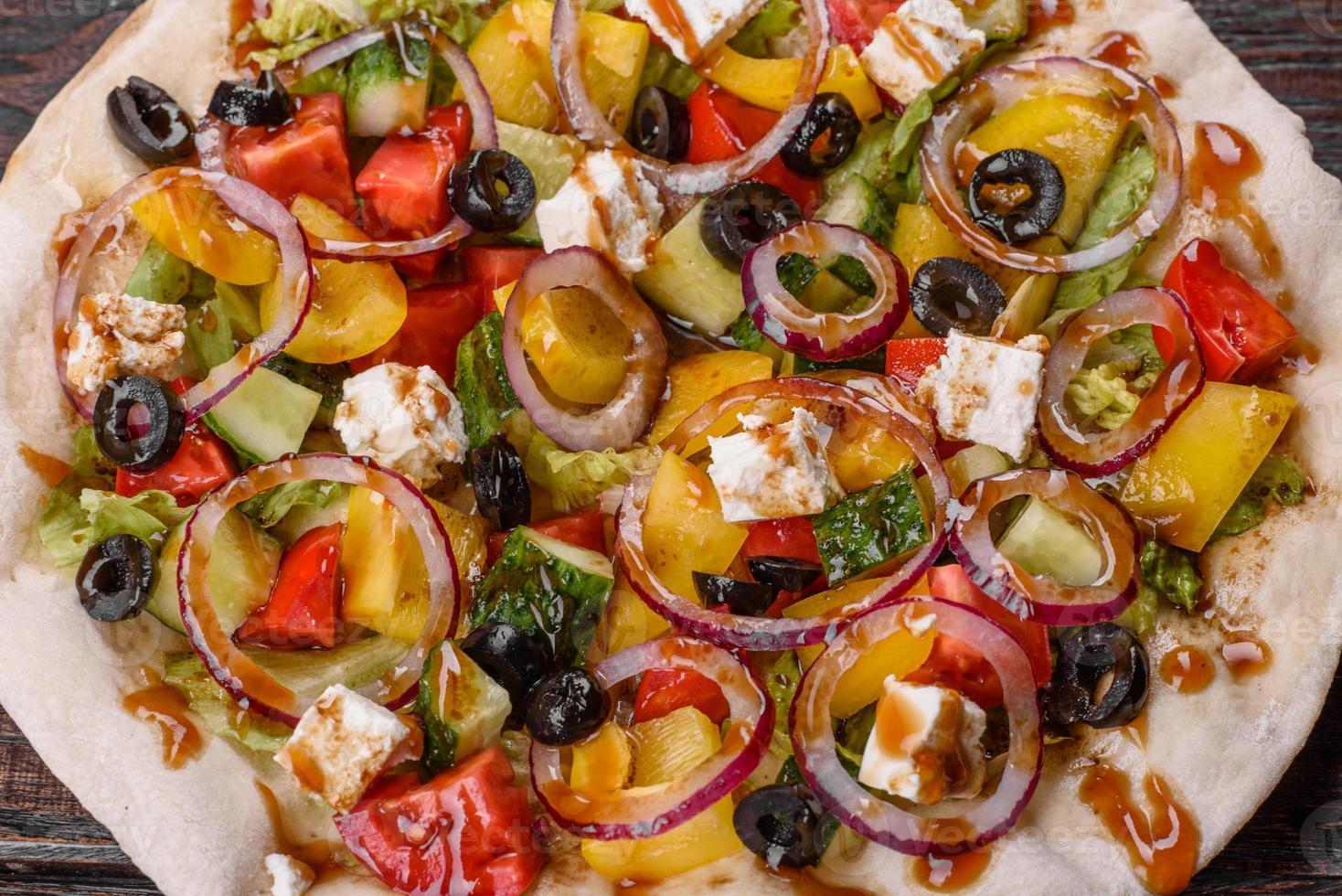 välsmakande färsk grekisk sallad på en pitabröd tillagad för ett festligt bord foto
