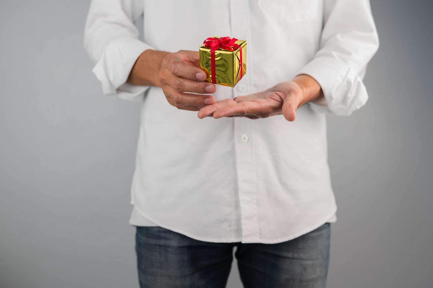 handhållande presentförpackning, nyårspresentlåda, julklappslåda, kopieringsutrymme. jul, hew år, födelsedagskoncept. foto
