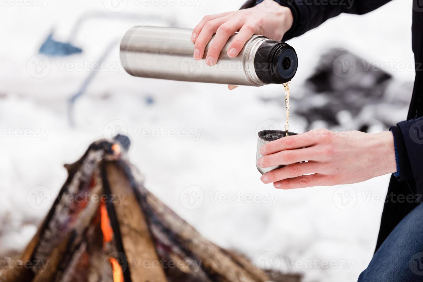 resenär händer man närbild häller te från kolvar i en kopp i skogen nära bål. foto