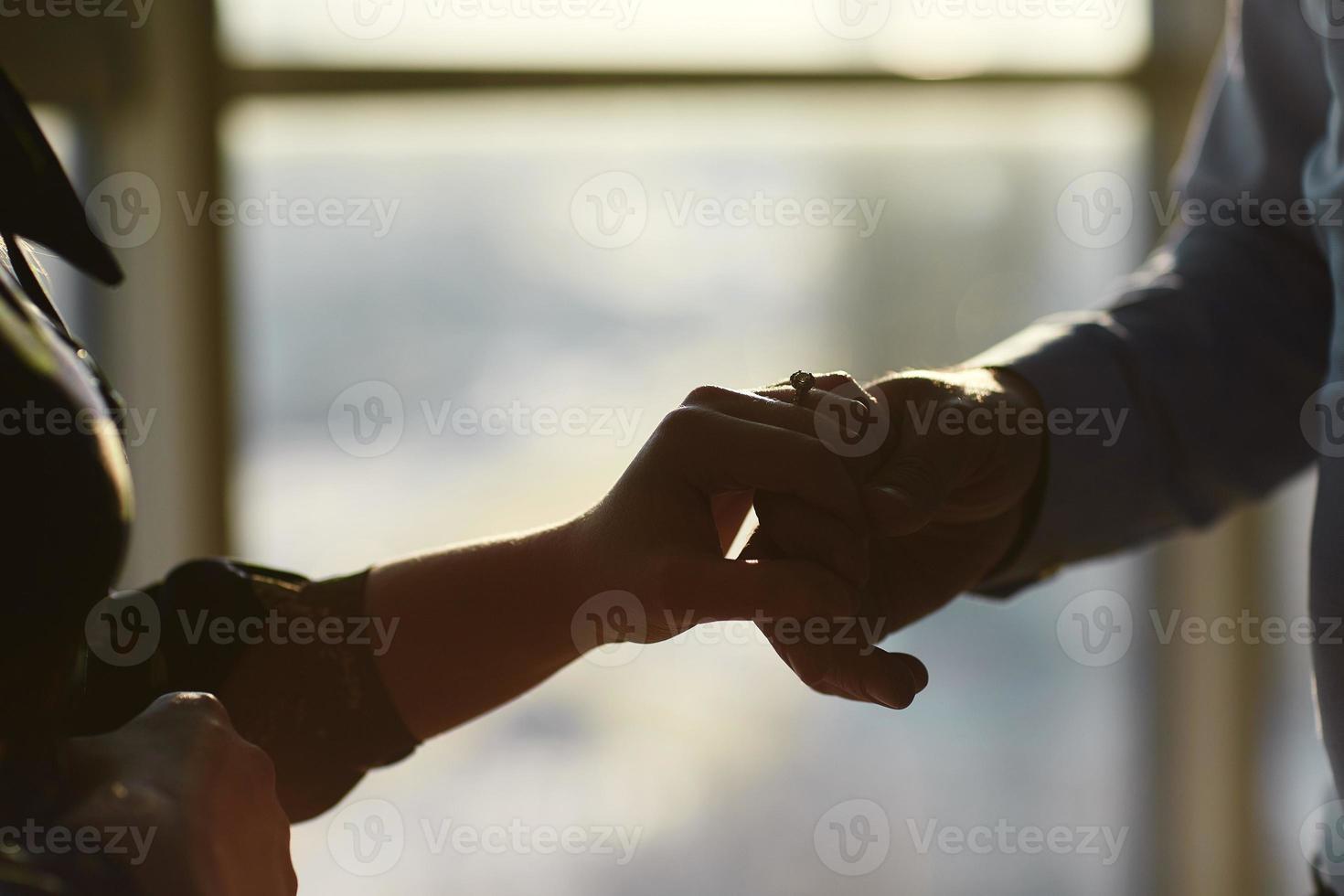 händer på ett ungt par med en ring. kärlek, par, relation och semester koncept - närbild av mannen som ger diamantring till kvinnan foto