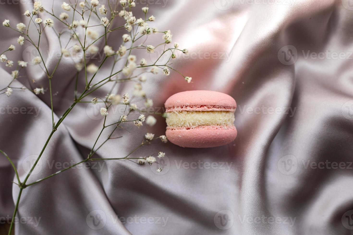 rosa franska makroner eller makronkakor och vita blommor på en tygbakgrund. naturlig frukt- och bärsmak, krämig fyllning för alla hjärtans mors dag påsk med kärleksmat. foto