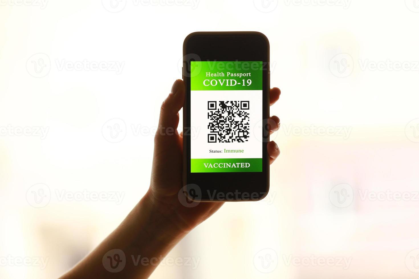 ett pass och en smart telefon med intyg om vaccination mot covid-19-sjukdomen. fokusera på smarttelefonen. hälsopass koncept. resa världen foto