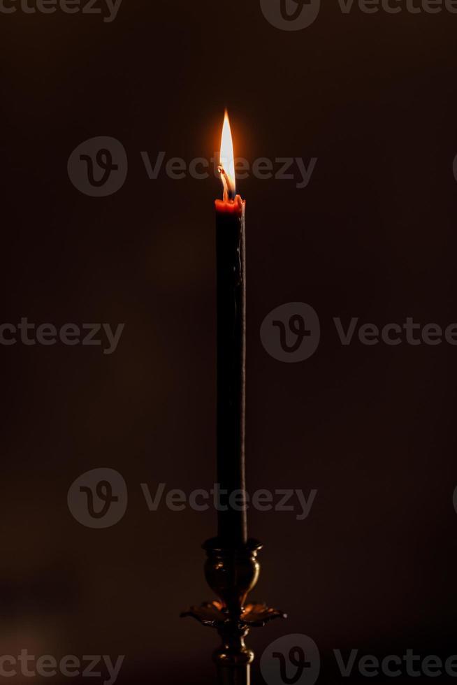 ett ljus som brinner på natten på den svarta bakgrunden i kyrkan. ljus isolerat i svart bakgrund. närbild. selektivt fokus foto