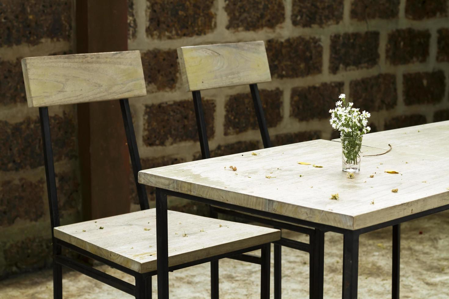 glas med blommor på vintage träbord foto