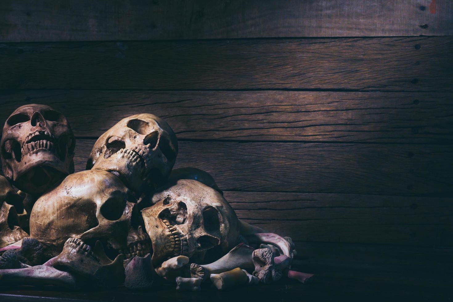stilleben fotografi med mänskliga skalle på gamla träbord bakgrund -halloween eller esoteriska koncept foto