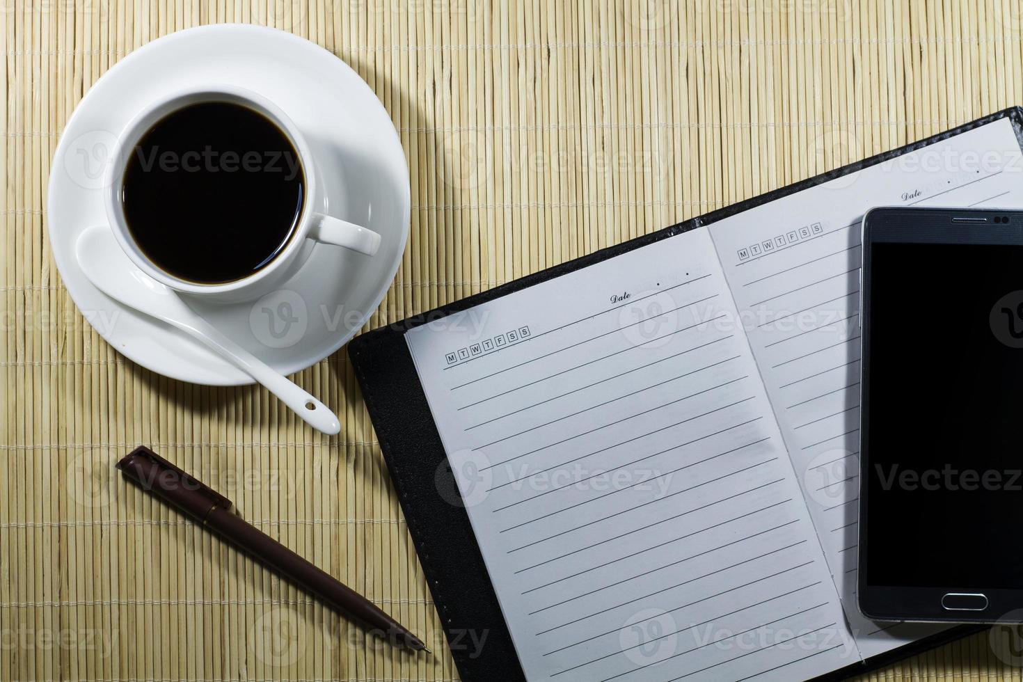 varm kaffekopp med anteckningsbok och mobil på skrivbordet affärsman foto