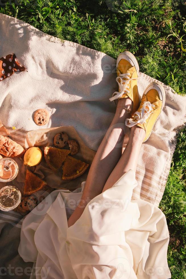 kvinna ben på filt med picknick på solnedgång mat dryck foto