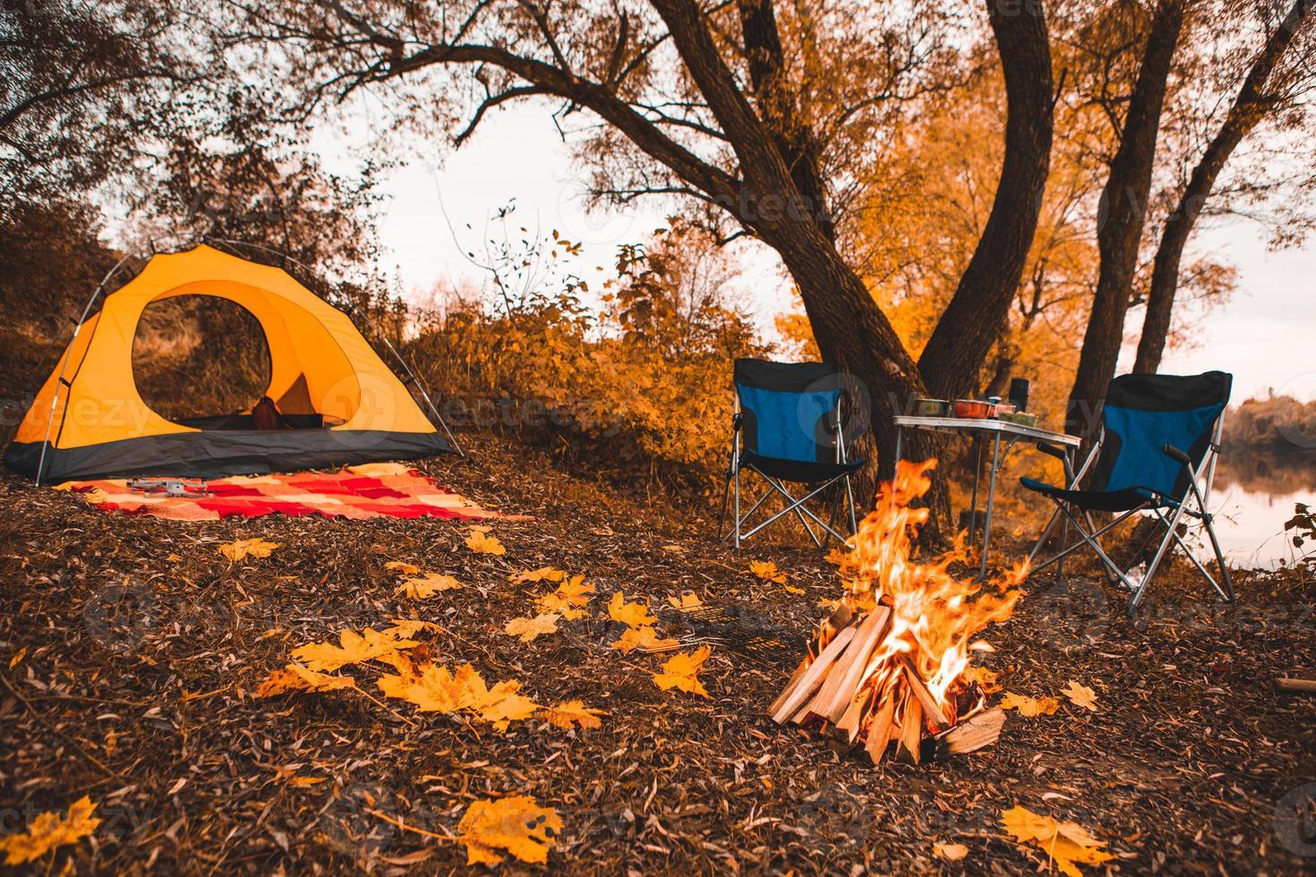 camping höstplats med brasa och bärbara stolar foto