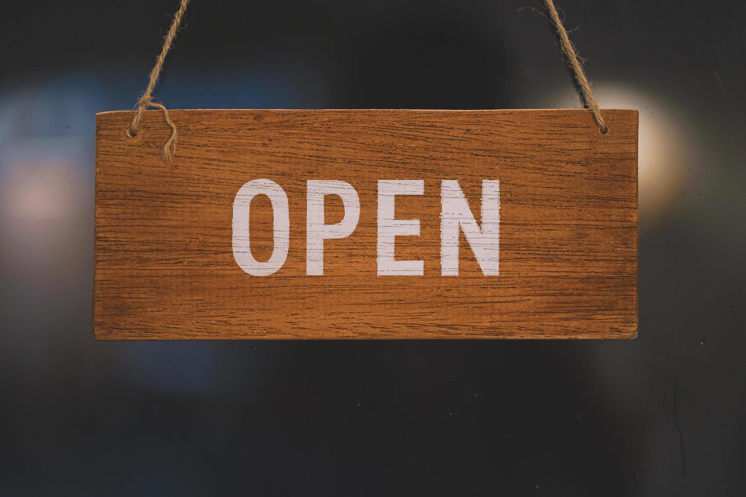 öppna träskylt brett genom dörren i caféet. affärsservice och matkoncept foto