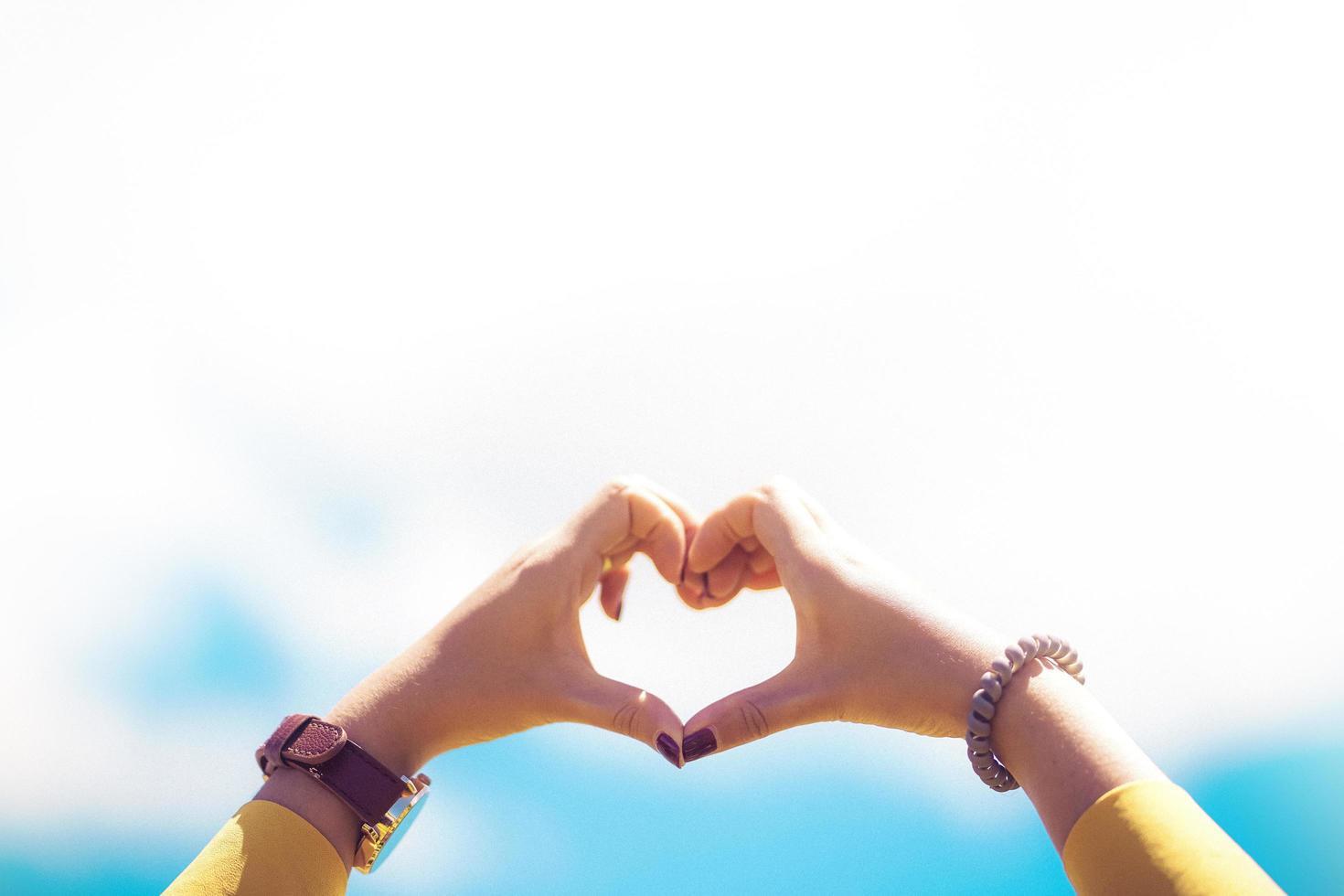 kvinnliga händer hjärta form inramning på blå himmel bakgrund foto