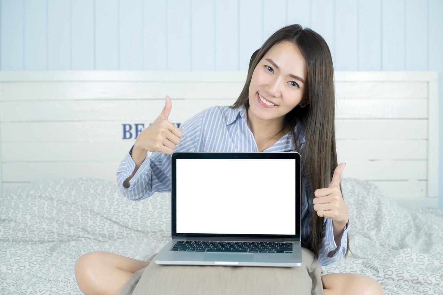 ung asiatisk kvinna leende och visar tom bärbar datorskärm i hennes sovrum foto