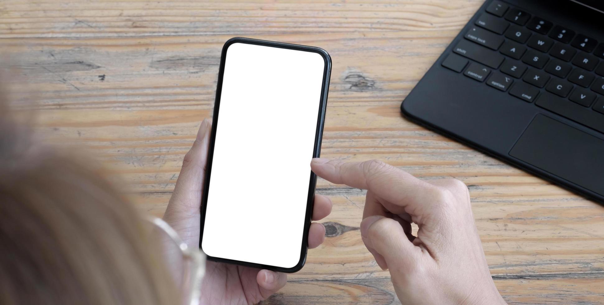 mockup bild tom vit skärm mobiltelefon. kvinnor hand håller textning med mobil på skrivbordet på hemmakontoret. foto
