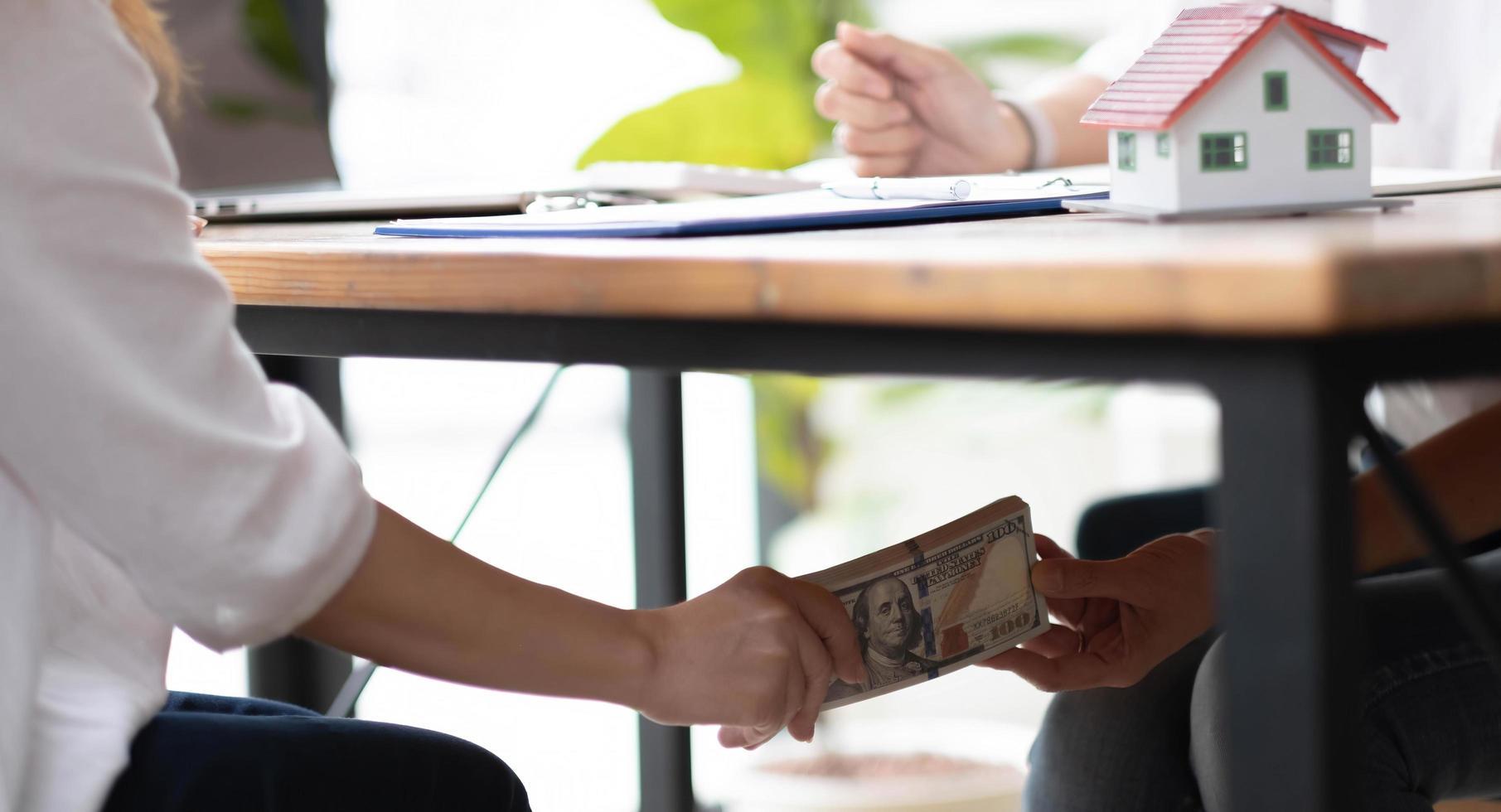 närbild affärskvinnor händer tar mutor pengar under bordet, korruption och mutor koncept foto