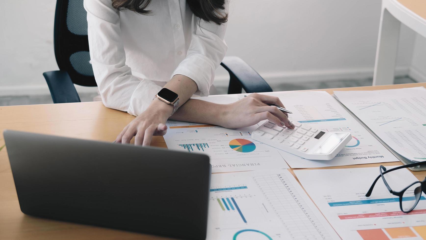 närbild ung affärskvinna som granskar projektekonomisk statistik, beräknar försäljning eller finansiella investeringar, analyserar ekonomiska grafer och diagram på datorn, hanterar budget. foto