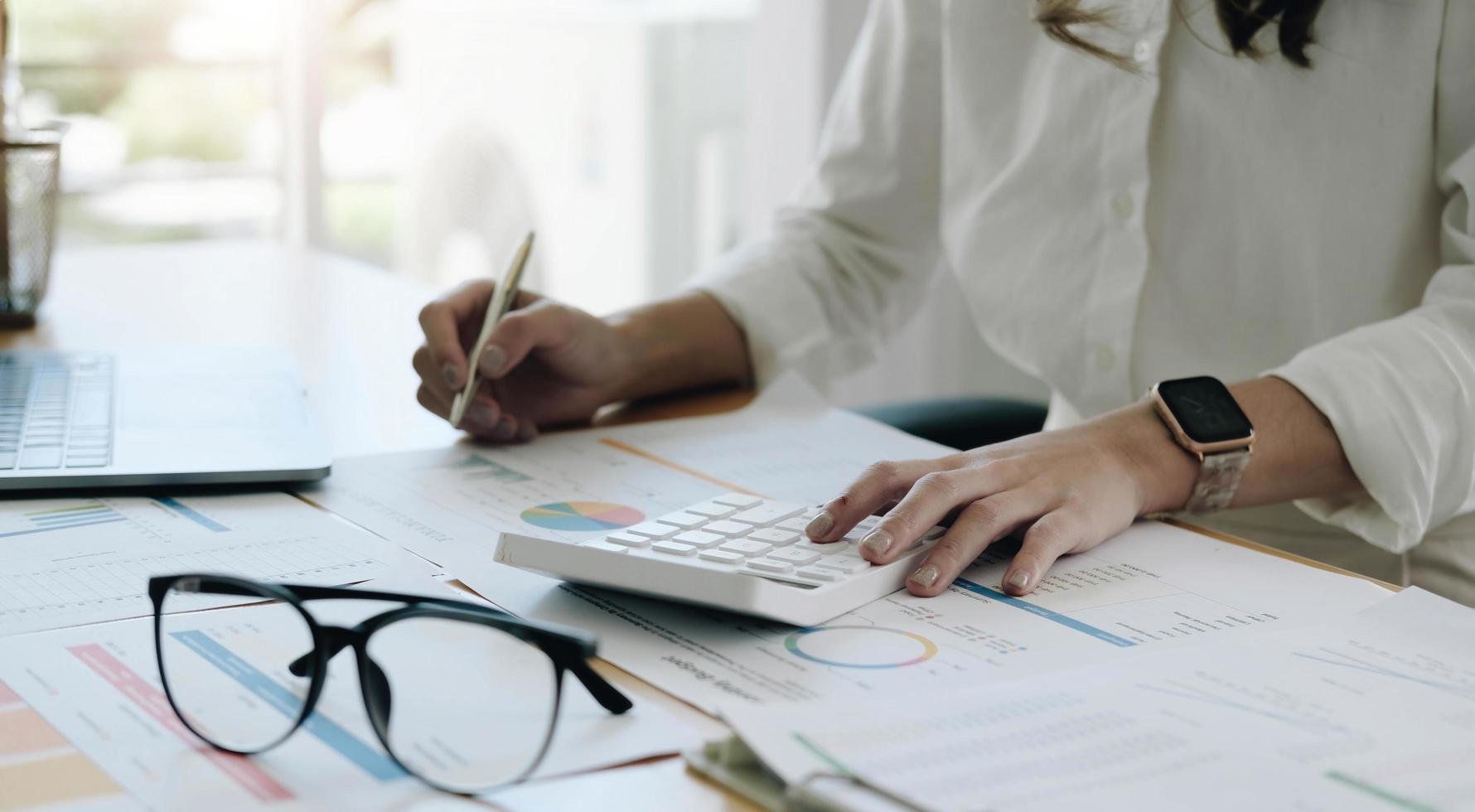 revisionsföretag, affärskvinnor finansinspektörsekreterare rapporterar om beräkning, kontroll av balans. intern inkomsttjänst inspekterar checkdokument med en bärbar dator och miniräknare. foto