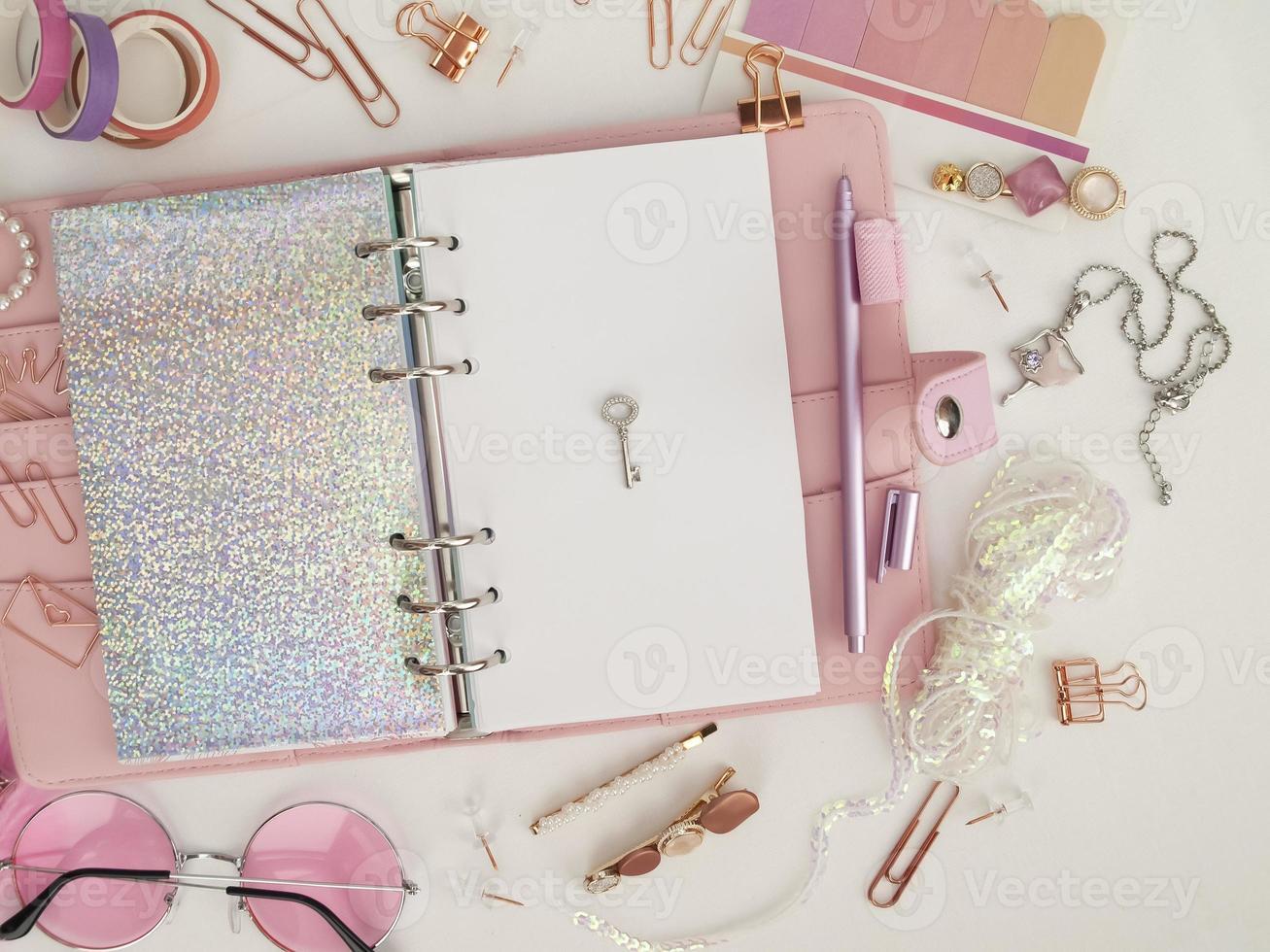 silvernyckel på planerarens vita sida. rosa glamourplanerare dekorationsfoto foto