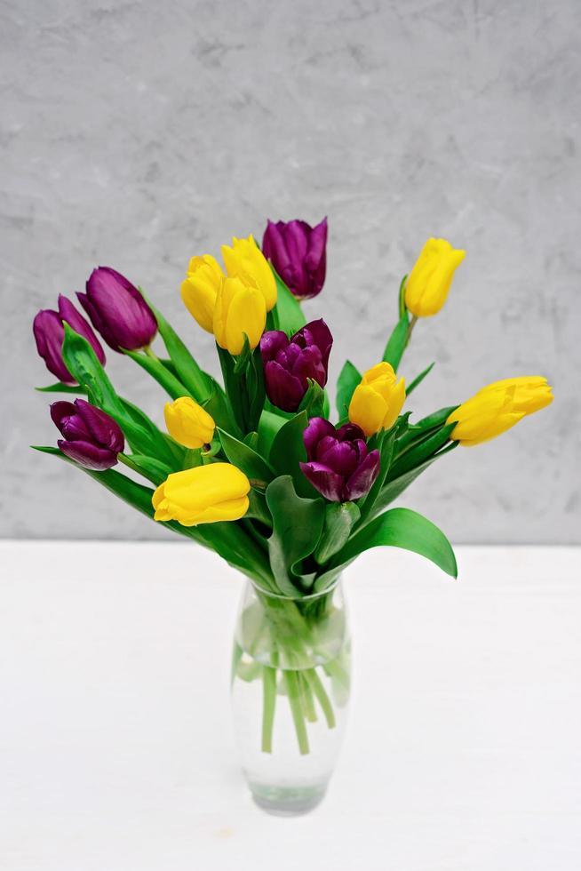 bukett lila och gula vårtulpanblommor i en glasvas på en ljus bakgrund. mors dag. internationella kvinnodagen. foto