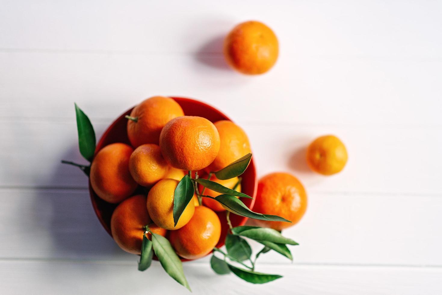mogna saftiga mandariner i en röd tallrik på en vit bakgrund. foto