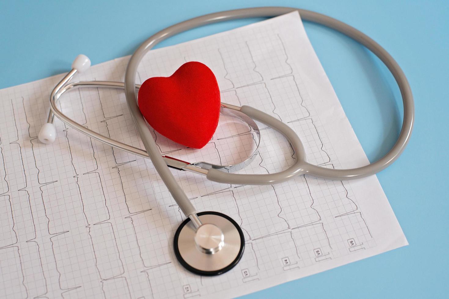 medicinsk stetoskop och rött hjärta som ligger på ett kardiogram. kardioterapeut, pulsmätare, hjärtfysik, foto